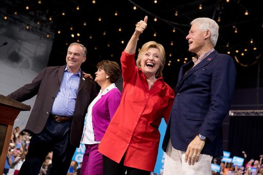 Democratic presidential candidate Hillary Clinton, second from right, accompanied by Democratic vice presidential candidate, Sen. Tim Kaine, D-Va., left, Tim Kaine's wife Anne Holton, second from left, and former President Bill Clinton, right, gives a thu