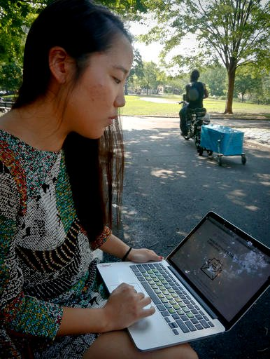In this Thursday July 21, 2016 photo, Korean American Jaime Sunwoo shows, from her laptop, a social media collaboration letter written by a host of Asian Americans and translated for their communities to discuss and support the Black Lives Matter movement