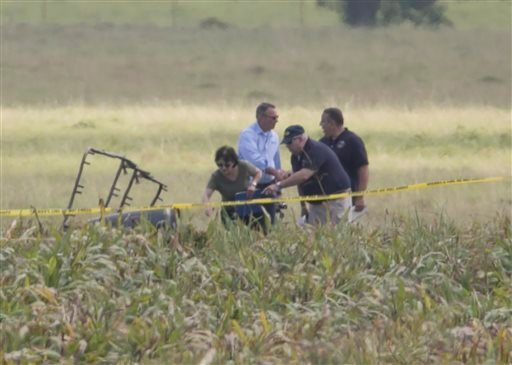 "The partial frame of a hot air balloon is visible above a crop field as investigators comb the wreckage of a crash Saturday, July 30, 2016, in Central Texas near Lockhart, Texas. Authorities say the accident caused a ""significant loss of life."" (Ralph Bar"