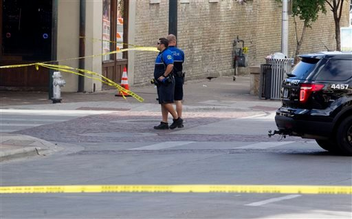 Police tape off areas on East 6th street in Austin, Texas, where a woman was fatally shot and several others wounded early Sunday, July 31, 2016. Police are still searching for the shooter, who opened fire in a crowded entertainment district in downtown A