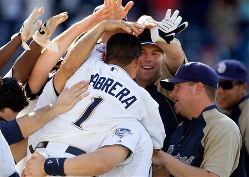 San Diego Padres' Everth Cabrera (1) is mobbed by his team after hitting the game winning RBI single in the tenth inning of a baseball game against the Arizona Diamondbacks Wednesday, Sept. 16, 2009 in San Diego.