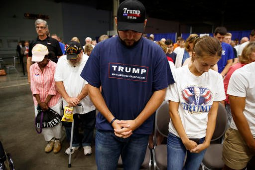 Supporters of Republican presidential candidate Donald Trump pray before the start of a town hall event, Monday, Aug. 1, 2016, in Columbus, Ohio . (AP Photo/Evan Vucci)