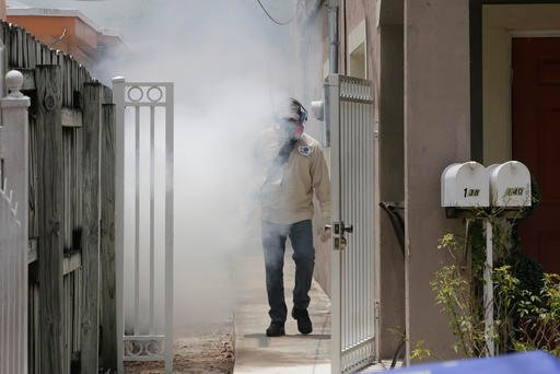 A Miami-Dade County mosquito control worker sprays around a home in the Wynwood area of Miami on Monday, Aug. 1, 2016.