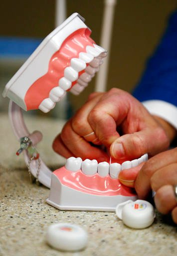 Dr. Wayne Aldredge, president of the American Academy of Periodontology, demonstrates how dental floss should be used in Holmdel, N.J. Aldredge says many people use floss incorrectly, moving it in a sawing motion instead of up and down the sides of the te