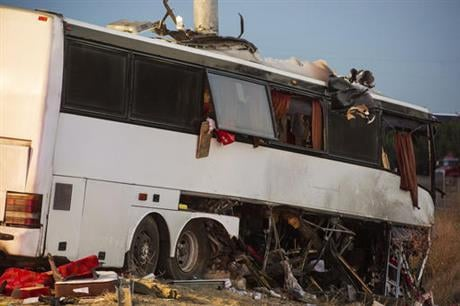 The bus veered off the central California freeway before dawn Tuesday and struck a pole that sliced the vehicle nearly in half, authorities said. (Andrew Kuhn/Merced Sun-Star via AP)