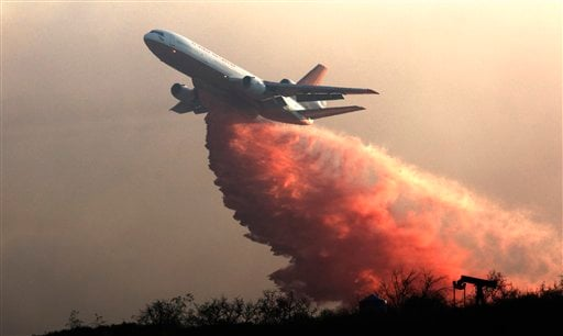 A DC-10 drops fire retardant over a hillside to battle wildfires in Grimes Canyon in Fillmore, Calif., on Tuesday, Sept. 22, 2009. (AP Photo/John Lazar)