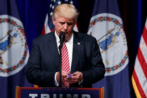 Republican presidential candidate Donald Trump holds a Purple Heart medal given to him by a supporter during a campaign rally.