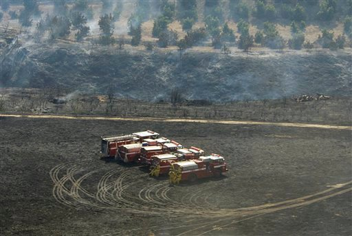 Fire trucks stand ready to move in a burned-over field near groves of trees in the upper Balcom Canyon area as efforts to fight the Guiberson Fire continue outside the Ventura County town of Moorpark, Calif., Wednesday, Sept. 23, 2009. (AP Photo/Reed Saxo