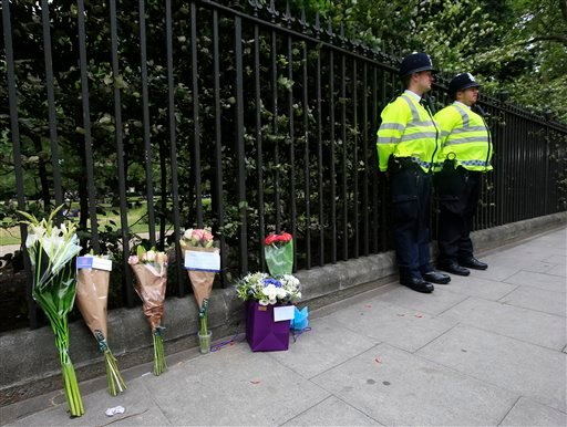 Floral tributes rest against railings Thursday Aug. 4, 2016, near the scene of a fatal stabbing on Wednesday night in Russell Square, London.