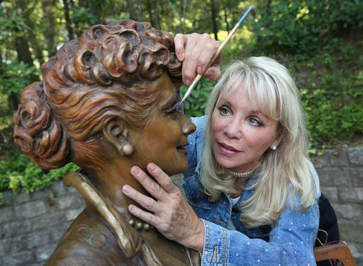 In this Wednesday, July 20, 2016 photo, artist Carolyn Palmer prepares to apply a cold patina to her bronze statue of Lucille Ball in Saddle River, N.J.