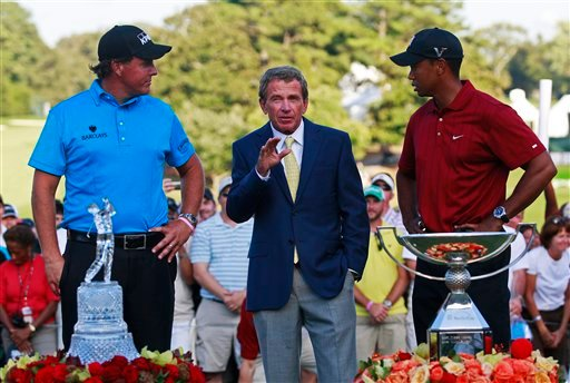 PGA Tour Tim Finchem, center, talks with The Tour Championship golf tournament winner Phil Mickelson, left, and FedEx Cup winner Tiger Woods following The Tour Championship at East Lake Golf Club in Atlanta Sunday, Sept. 27, 2009. (AP Photo/Dave Martin)