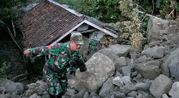 Indonesian soldiers climb rocks from an earthquake-triggered landslide in Cianjur, West Java, Indonesia, Thursday, Sept. 3, 2009 as they survey the damage. At least dozens of people were killed and another dozens were missing after a strong earthquake roc