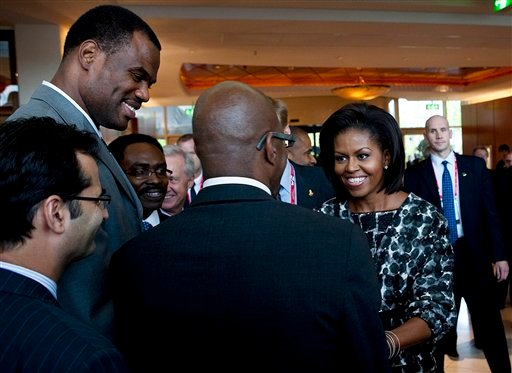 U.S. first lady Michelle Obama greets U.S. track great Ed Moses, center, as former NBA player David Robinson, top left, looks on at a hotel in Copenhagen before she meets with International Olympic Committee (IOC) members in Copenhagen.