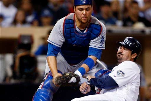 San Diego Padres' Adrian Gonzalez is tagged out by Los Angeles Dodgers' Russell Martin while trying to score from second on a single to center.