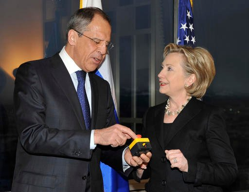"In this March 6, 2009 file photo, then-Secretary of State Hillary Clinton presents Russian Foreign Minister Sergey Lavrov with a device with a red button symbolizing the intention to ""reset"" U.S.-Russian relations during their meeting in Geneva, Switzerla"