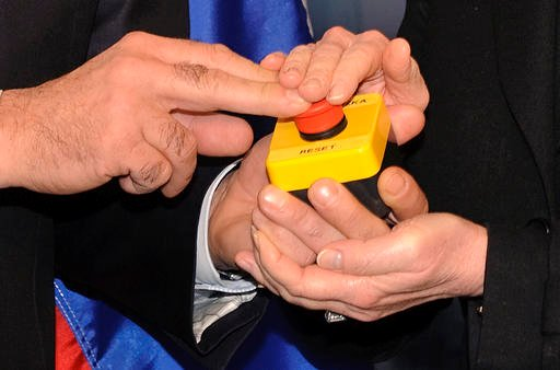 """In this March 6, 2009, file pool photo, then-Secretary of State Hillary Clinton and Russian Foreign Minister Sergei Lavrov hold together a device a with a red button symbolizing the intention to """"reset"""" U.S.-Russian relations during their meeting in Genev"""