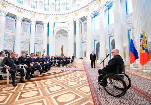 In this file photo taken on Monday, March 24, 2014, Sir Philip Craven, President of the International Paralympic Committee, right, speaks as Russian President Vladimir Putin, standing background center, listens to him during an awards ceremony in the Krem