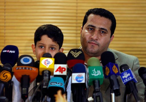 In this file photo taken on Thursday, July 15, 2010, Shahram Amiri, an Iranian nuclear scientist attends a news briefing while holding his son Amir Hossein as he arrives at the Imam Khomeini airport just outside Tehran, Iran, after returning from the Unit