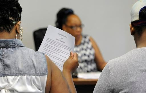 In a June 18, 2016 photo, Virginia Stephens, center, who is a home buyer counselor at Detroit Non-Profit Housing Corp., waits for two women to read information about what they need to buy their first home, in Detroit. Both women declined to be identified.