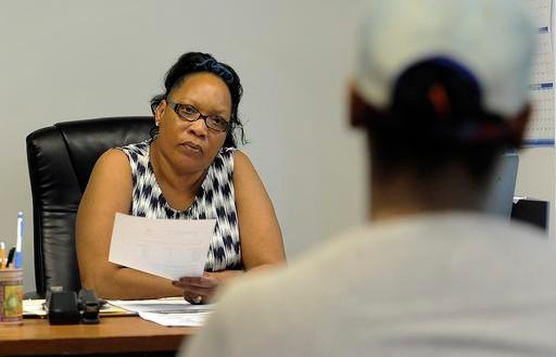 In a June 18, 2016 photo, Virginia Stephens, left, who is a home buyer counselor at Detroit Non-Profit Housing Corp., talks to a woman about what she needs to buy her first home, in Detroit. It and other nonprofits are the final options for hundreds of De