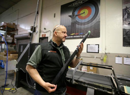 In this June 14, 2016, photo George A. Tekmitchov, of Easton Technical Products, holds arrows at Easton where their arrows are made in Salt Lake City. As the story goes, the company's founder, Doug Easton, was duck hunting one fall day in 1921, when he le