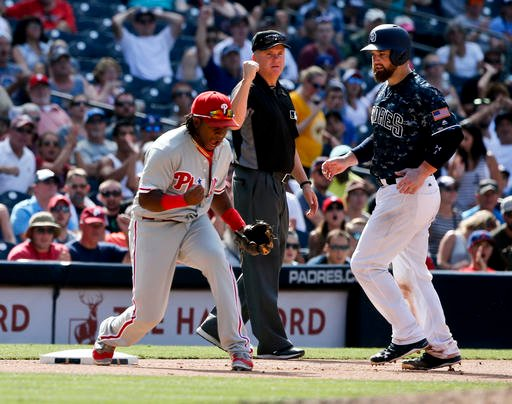 Philadelphia Phillies third baseman Maikel Franco, left, pumps his fist after a Phillies triple play against the San Diego Padres in the seventh inning of a baseball game Sunday, Aug. 7, 2016, in San Diego. Umpire Mike Everett, center, and Padres' Derek N