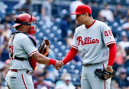 Philadelphia Phillies closer Jeanmar Gomez and catcher Carlos Ruiz congratulate each other after the Phillies' 6-5 victory over the San Diego Padres in a baseball game, Sunday, Aug. 7, 2016, in San Diego. (AP Photo/Lenny Ignelzi)