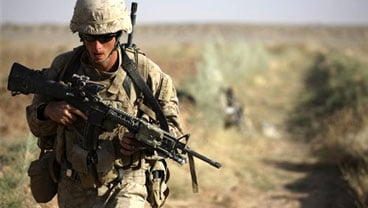 US Marine Cpl. Matthew Doherty, of Bastrop, Texas, with 3rd Platoon, Bravo Company, 1st Battalion 5th Marines, walks on a joint patrol with the Afghan Army, in Nawa district, Helmand province, southern Afghanistan, Oct. 4, 2009. (AP Photo/Brennan Linsley)