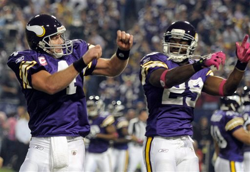 Minnesota Vikings' Brett Favre (4) celebrates with Chester Taylor (29) after Favre threw a touchdown pass during the first half of an NFL football game against the Green Bay Packers Monday, Oct. 5, 2009, in Minneapolis. (AP Photo/Tom Olmscheid)