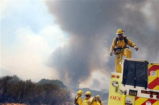 A strike team prepares to deploy along Highway 173 during a wildfire in Hesperia, Calif., on Monday, Aug. 8, 2016.