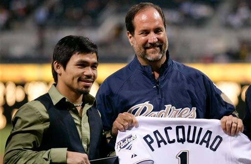 FILE PHOTO: San Diego Padres CEO Jeff Moorad, right, holds up a jersey next to boxer Manny Pacquiao, left.