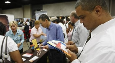 In this Sept. 15, 2009 photo, Wilbert Woodward fills out an application for United Parcel Service during a job fair sponsored by the National Urban League in Louisville, Ky. Woodward said he had been looking for a job for five months. The number of newly