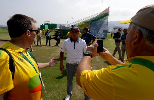 Volunteers greets Rickie Fowler, of the, United States, after a practice round for men's golf event at the 2016 Summer Olympics in Rio de Janeiro, Brazil, Tuesday, Aug. 9, 2016.