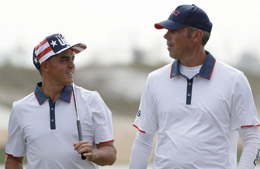Rickie Fowler, of the United States, left talks to Matt Kuchar, of the, United States, as they walk off the second green during a practice round for the men's golf event at the 2016 Summer Olympics in Rio de Janeiro, Brazil, Tuesday, Aug. 9, 2016.