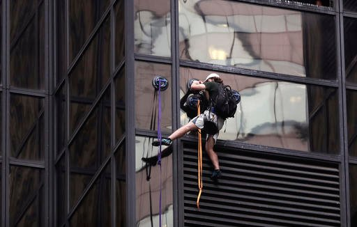 A man scales the all-glass facade of Trump Tower, Wednesday, Aug. 10, 2016, in New York. The 58-story building is headquarters to the Republican presidential nominee's campaign. He also lives there. (AP Photo/Julie Jacobson)