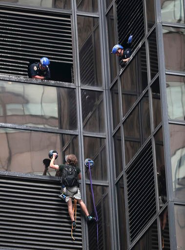 A man scales the all-glass facade of Trump Tower, Wednesday, Aug. 10, 2016, in New York. A police spokeswoman says officers responded to Donald Trump's namesake skyscraper on Fifth Avenue in Manhattan. The 58-story building is headquarters to the Republic