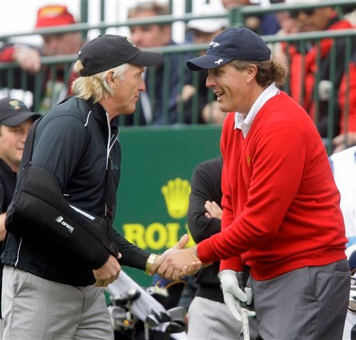 International captain Greg Norman, left, shakes hands with United States player Phil Mickelson at the first tee for foursomes matches at the Presidents Cup golf matches at Harding Park Golf Course Thursday, Oct. 8, 2009, in San Francisco. (AP Photo/Jeff C