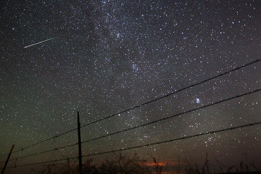 In this early morning, Aug. 13, 2013 file photo, a meteor streaks past the faint band of the Milky Way galaxy above the Wyoming countryside north of Cheyenne, Wyo.