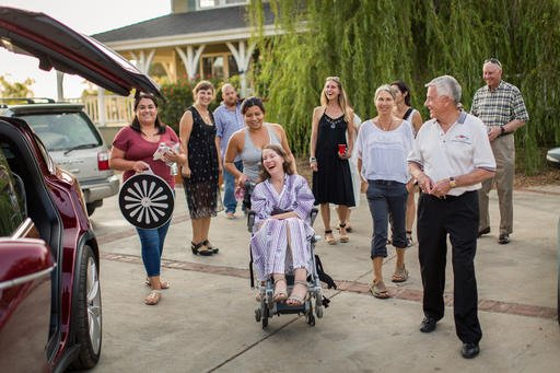 """This July 24, 2016 photo provided by Niels Alpert, Betsy Davis, center, is accompanied by friends and family for her first ride in a friends new Tesla to a hillside to end her life during a """"Right To Die Party"""" in Ojai, Calif. In early July, Davis emailed"""