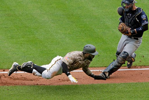 Pittsburgh Pirates' Josh Harrison, bottom, tries unsuccessfully to get around San Diego Padres catcher Derek Norris after being caught in a rundown between third and home in the fourth inning a baseball game in Pittsburgh, Thursday, Aug. 11, 2016.