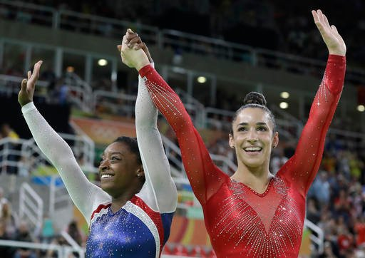 United States' Simone Biles, left, and Aly Raisman celebrate after winning gold and silver respectively for the artistic gymnastics women's individual all-around final at the 2016 Summer Olympics in Rio de Janeiro, Brazil, Thursday, Aug. 11, 2016.