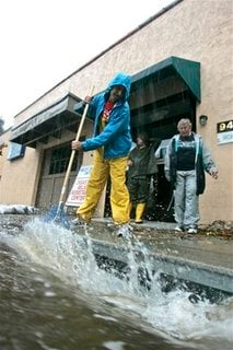 Dennis Marcum, left, clears a storm drain as his mother Annette Marcum looks on outside of the Valley Churches United Missions building in Ben Lomond, Calif. on Tuesday, Oct. 13, 2009. Residents across California braced for possible flash floods and mudsl
