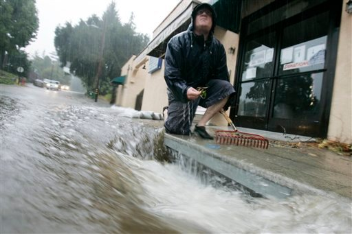 Chris Wright kneels next to a clogged storm drain as rain falls in Ben Lomond, Calif. on Tuesday, Oct. 13, 2009. (AP Photo/Marcio Jose Sanchez)