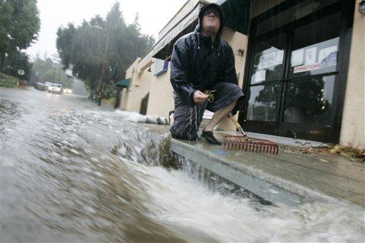 Chris Wright kneels next to a clogged storm drain as rain falls in Ben Lomond, Calif. on Tuesday, Oct. 13, 2009. (AP Photo/Marcio Jose Sanchez)