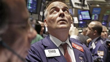 Trader Albert Young works on the floor of the New York Stock Exchange Wednesday, Oct. 14, 2009. (AP Photo/Richard Drew)