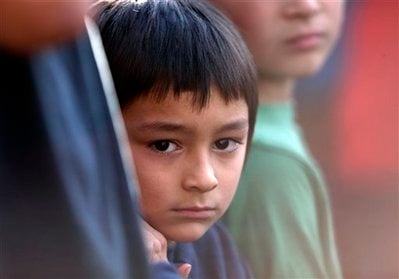 Six-year-old Falcon Heene peeks out from behind the leg of his father, Richard, during a news conference outside the family's home in Fort Collins, Colo., after Falcon Heene was found hiding in a box in a space above the garage on Thursday, Oct. 15, 2009.