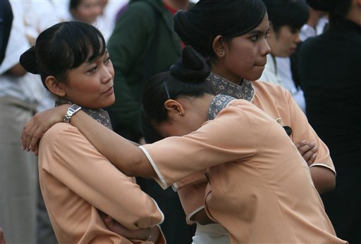 A hotel worker leans on her colleague as they are evacuated outside their building after a preliminary magnitude 6.4 earthquake was felt in Jakarta, Indonesia, Friday, Oct. 16, 2009. (AP Photo/Achmad Ibrahim)