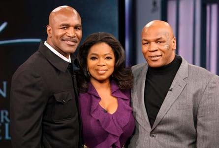 """In this photo provided by Harpo, Inc., talk-show host Oprah Winfrey poses with former world champion boxers Mike Tyson, right, and Evander Holyfield on a live episode of """"The Oprah Winfrey Show,""""  (AP Photo/Harpo Productions, Inc. George Burns)"""