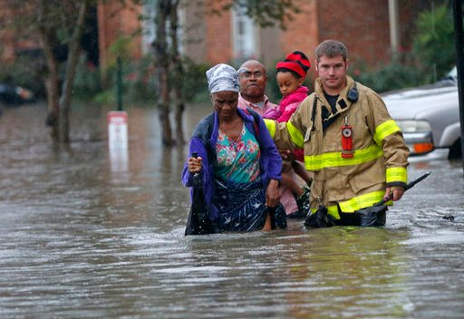 A member of the St. George Fire Department assists residents as they wade through floodwaters.