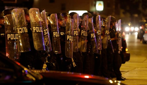 Police move in on a crowd throwing rocks at police in Milwaukee, Sunday, Aug. 14, 2016. Shots rang out during unrest after a police shooting that killed a man Saturday. (AP Photo/Jeffrey Phelps)